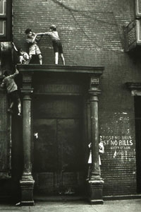 Photo of two children playing on a precarious ledge in New York City.