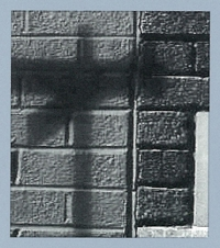 Black and white photo of the shadow of a street sign against a brick wall.